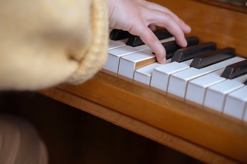 High angle of crop anonymous female pianist sitting at piano and pressing keys while practicing music