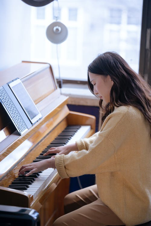 Asian female playing piano during rehearsal