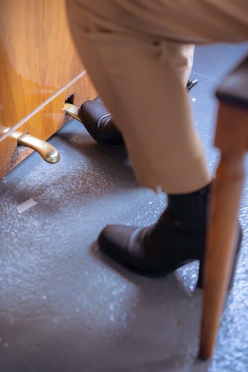 Stylish woman stepping on piano pedal