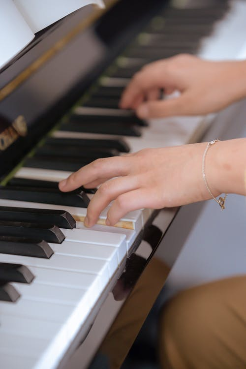 Young lady gently pressing piano keys