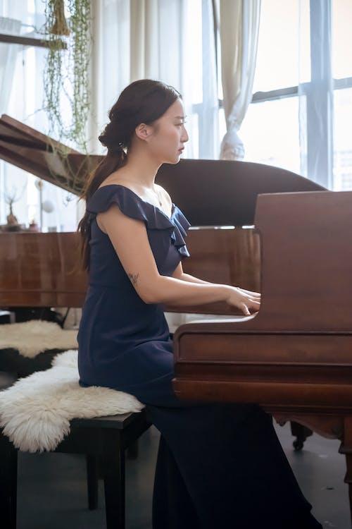 Elegant Asian woman playing grand piano