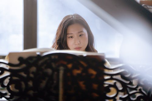 Young dreamy ethnic female attentively looking in music book located on carved stand while playing piano in light studio with big window