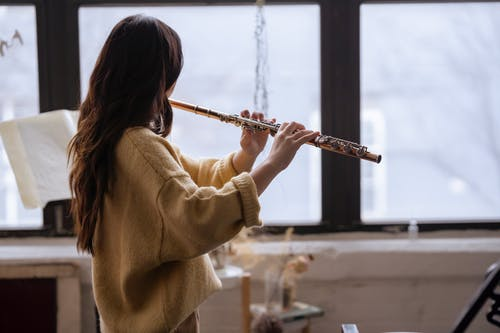 Side view of anonymous lady in casual sweater playing flute while standing near windows in light room