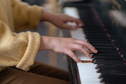 Side view of crop anonymous lady in casual outfit sitting in light room while playing piano