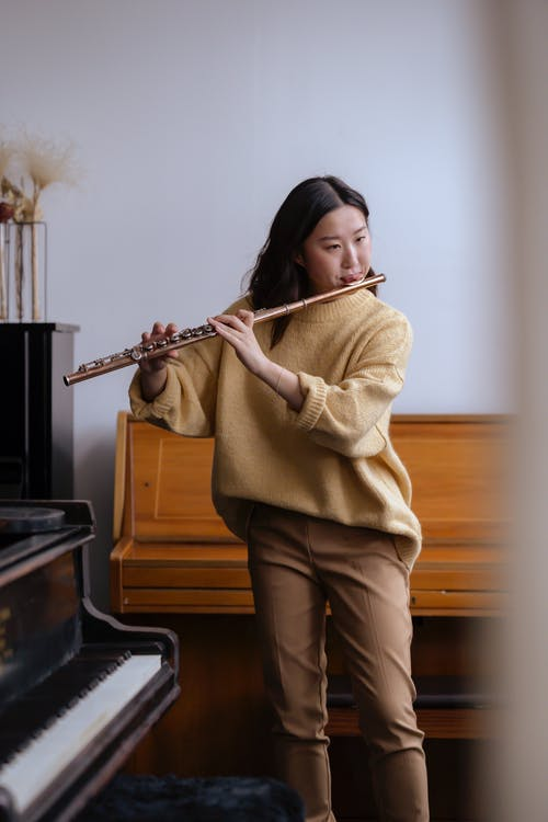 Asian woman playing flute near piano in studio