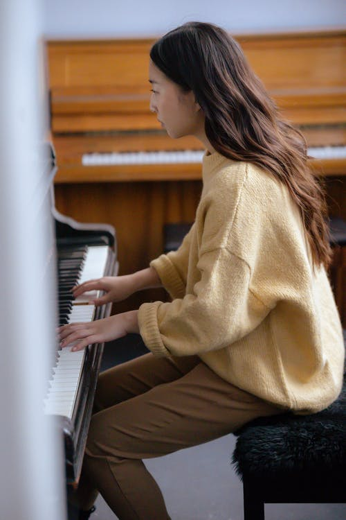 Side view of concentrated young Asian lady in casual clothes playing piano while sitting on pouf in bright studio
