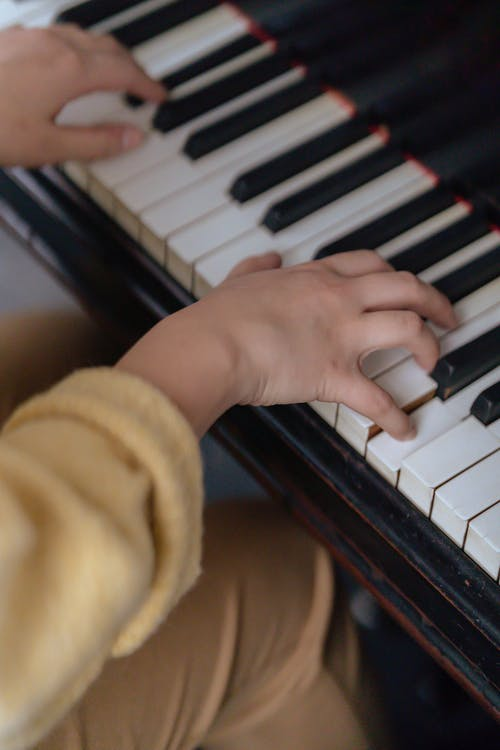High angle of crop anonymous female in casual outfit sitting in light room and playing piano