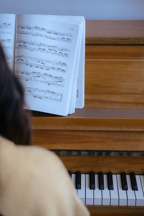 Back view of crop anonymous female in casual outfit playing on wooden piano with music book in light room