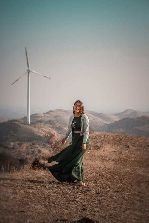 Full body of positive Indian female looking at camera while standing against tall wind generator and mountainous area in nature