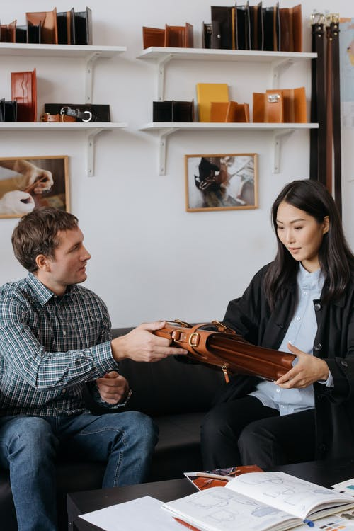 Man Sitting Beside a Woman Holding Brown Leather Bag
