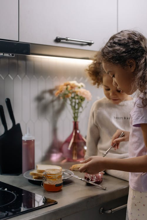 Two Girls Making Jam Sandwiches