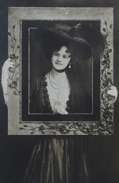 Old Photo Of Woman Holding A Frame And Covering Her Face