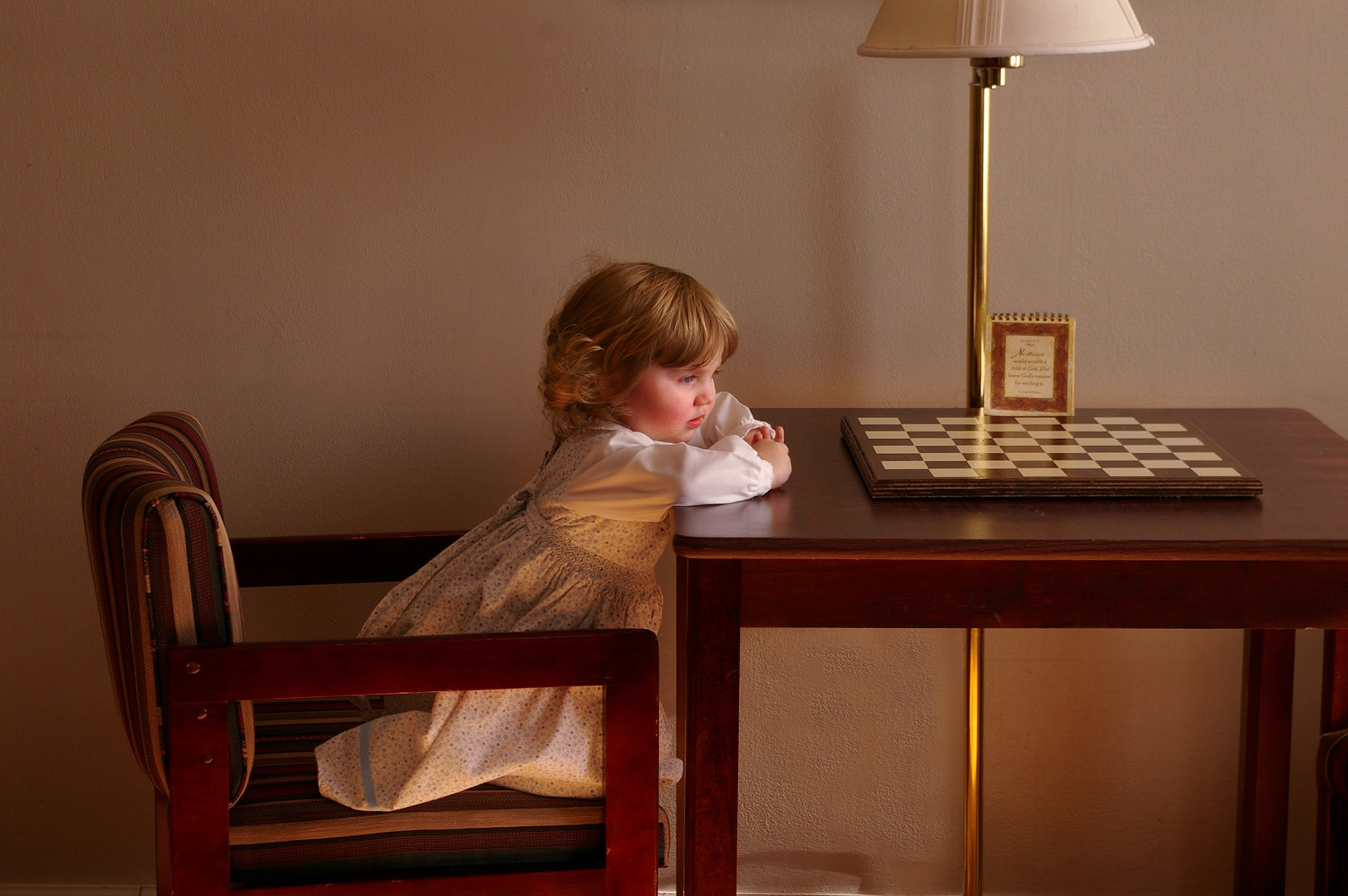 Child Setting on Chair in Front of Table