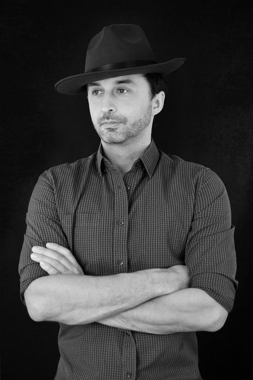 Black and white of wistful young man in trendy hat and shirt standing in dark studio with folded arms and looking away