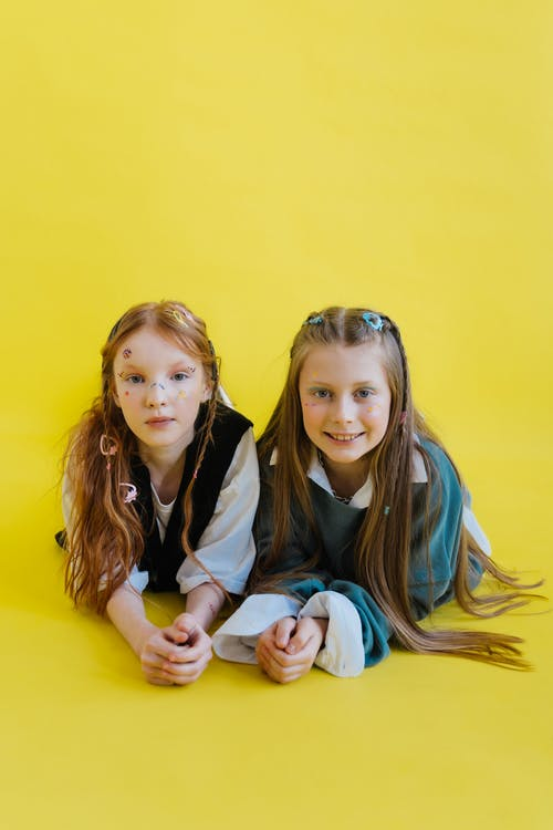 Two Girls on Yellow Surface