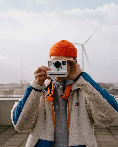 Anonymous guy taking photos on film camera against wind mills