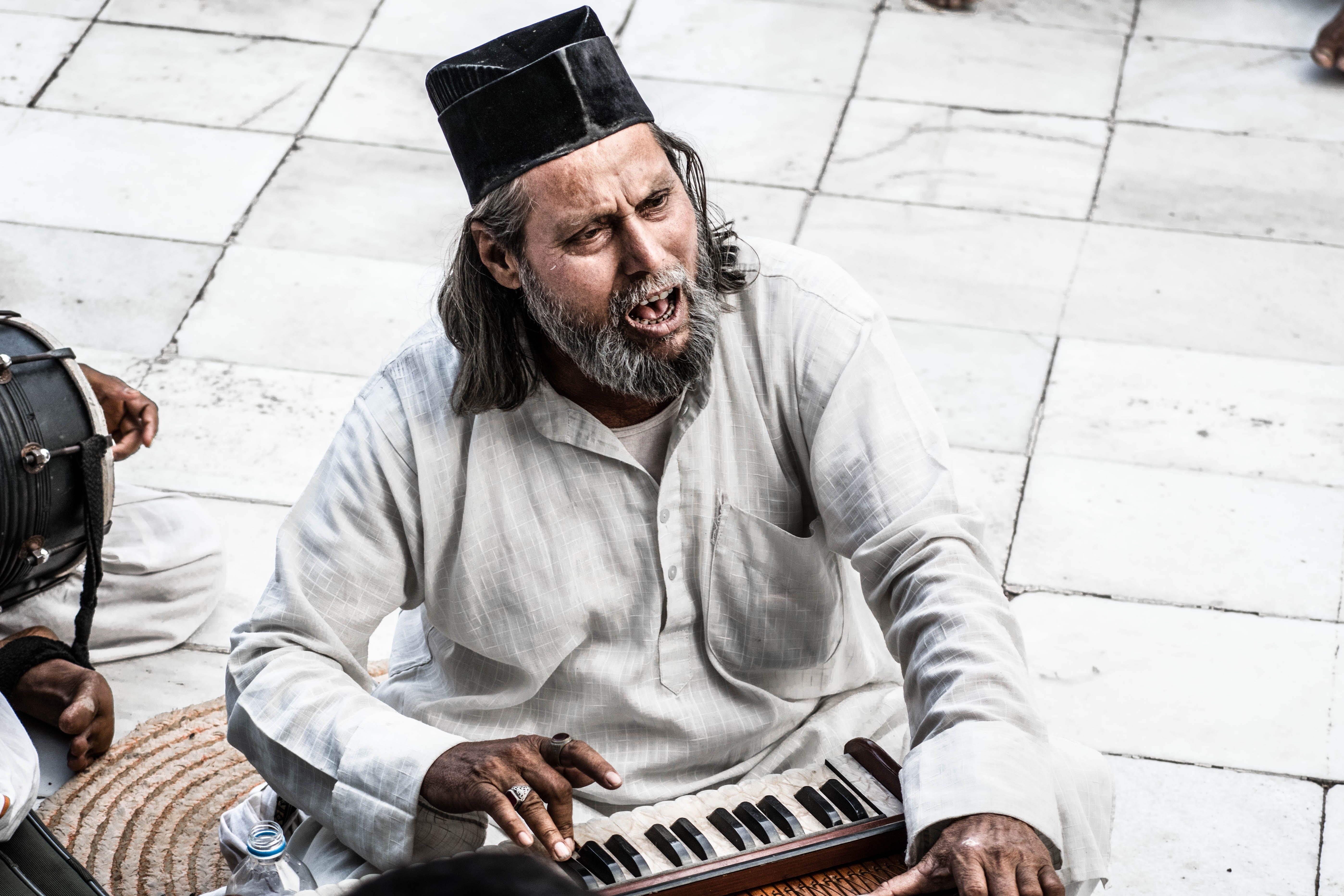 Man Sitting Holding Instrument
