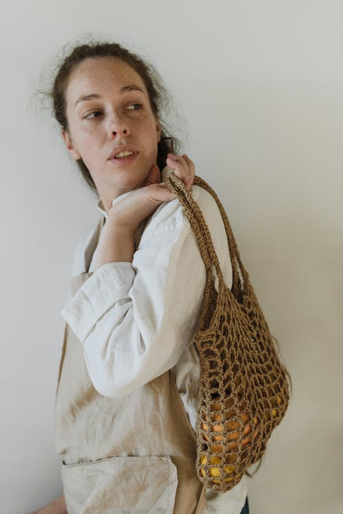 Attentive young lady carrying cotton bag with fresh groceries and looking away