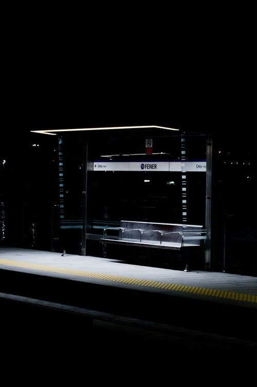 Modern glass bus stop illuminated with light at night
