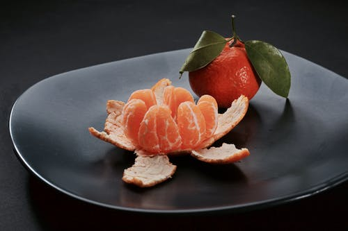 Close-Up Photo of Two Clementines on a Black Plate