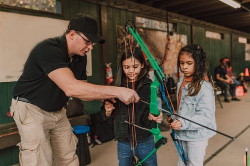 Adult male archery coach teaching adorable little multiethnic girls to shoot with bow and arrow during classes in range