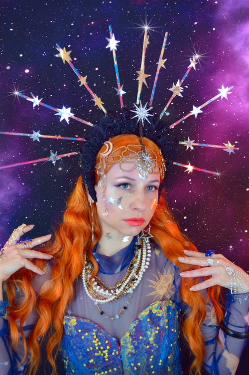 Self assured young female magician in dress with shining headband touching long red hair and looking away against purple starry sky