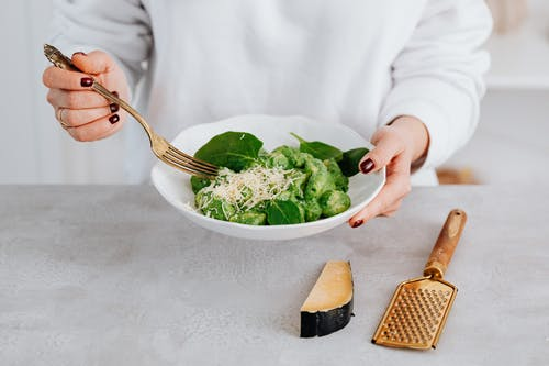 Person Holding Stainless Steel Fork and Green Vegetable on White Ceramic Bowl