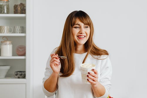 Woman with Brown Hair Holding a White Cup with Ice Cream while Smiling