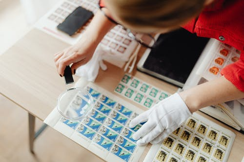 A Woman Using a Magnifying Glass on Postage Stamps