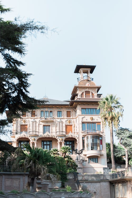 Low angle exterior of aged classic Villa Grock with arched windows and observation tower against cloudless blue sky in Imperia