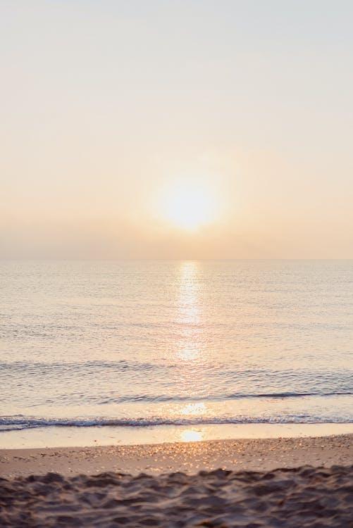 Sun setting over waving sea with sandy shore