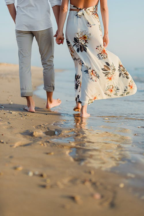Anonymous romantic couple holding hand and walking on sandy seashore