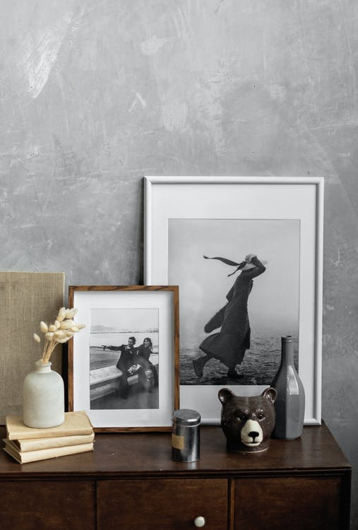 Framed black and white photos and decorative elements arranged on wooden cabinet near vase with dry reeds placed on stack of books