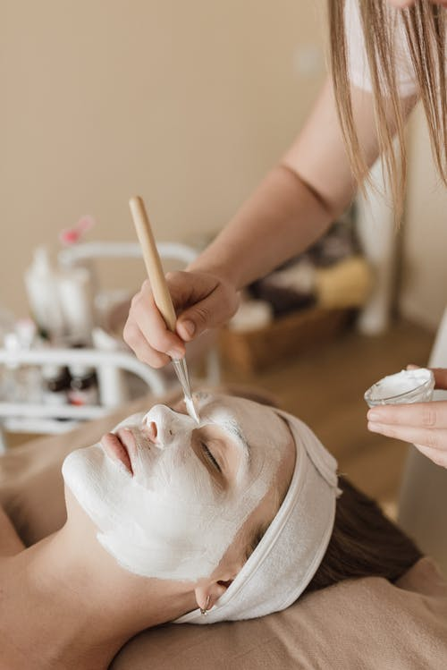 A Person Applying Facial Mask on a Womans Face