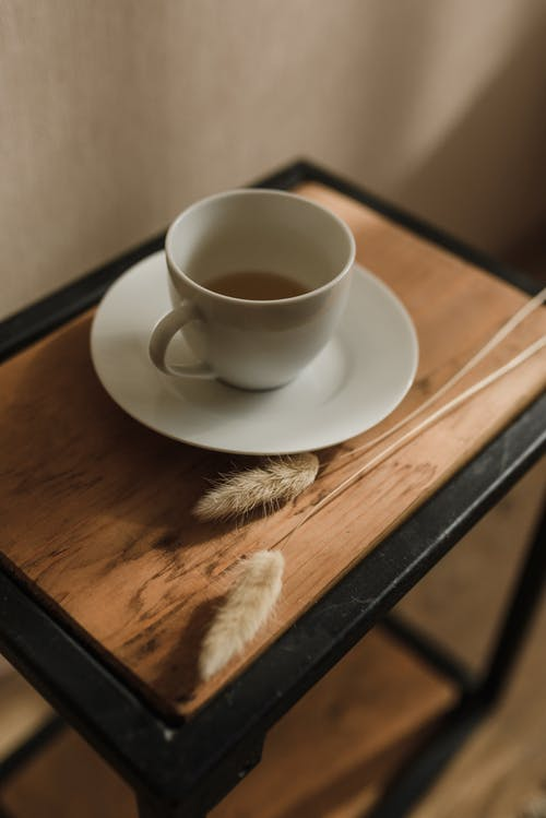 Cup of tea served on wooden table near dry plant spikelets