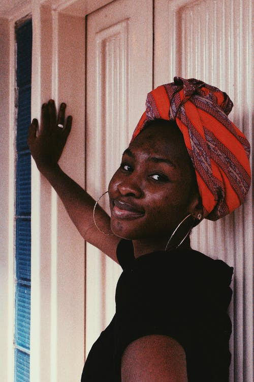 Optimistic African woman looking at camera while standing at home and leaning on wall with hand