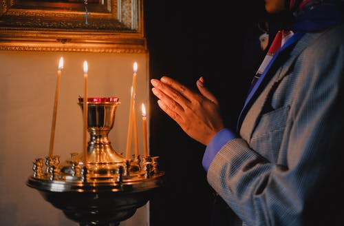 Man in Blue Suit Jacket Holding Candle Holder