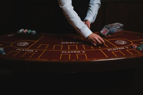Person in White Pants and White Long Sleeve Shirt Playing Game Board