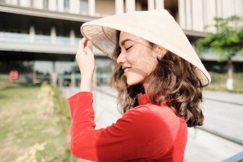 Cheerful Asian woman in Vietnamese hat standing on street