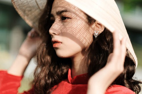 Crop beautiful young Asian female wearing traditional Vietnamese hat and touching brims while standing on sunny street