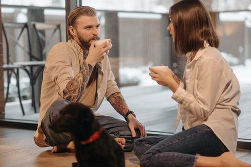 Couple Drinking Coffee Sitting Beside a Dog