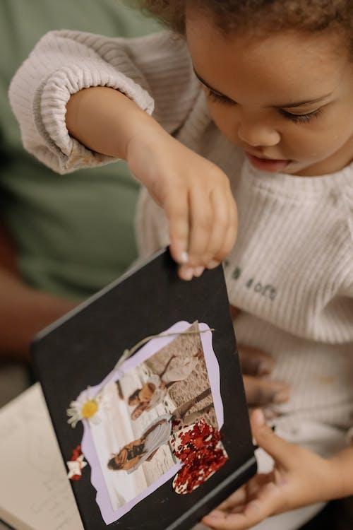 Child in White Sweater Holding a Photo Album