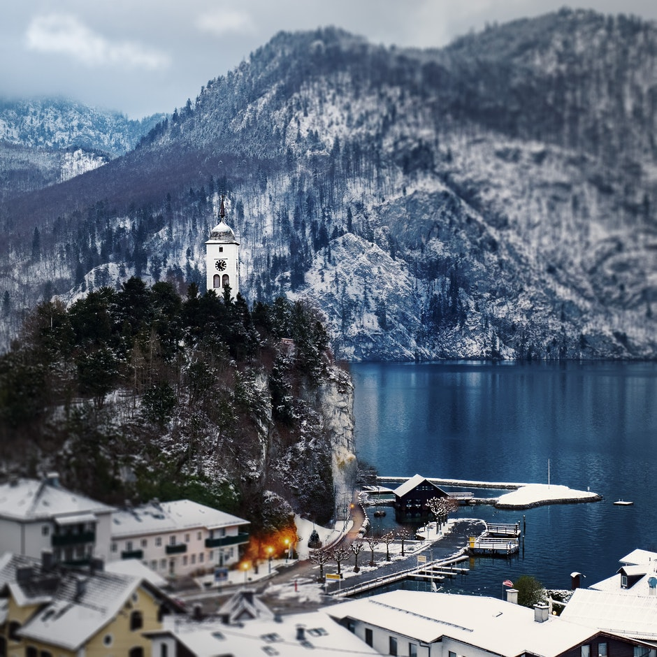 Snow Covered Mountain Houses Near Body of Water at Daytime