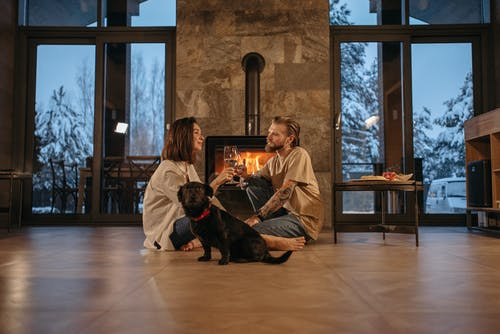 Couple with a Dog Sitting Near Fireplace