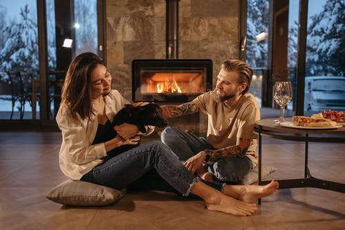 Man and Woman Sitting on Floor Beside Fireplace