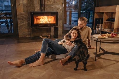 Couple with a Dog Sitting Beside the Fireplace