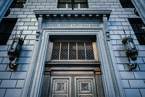 From below classic styled historic building of United States National Bank with wooden doors and vintage lanterns located in Portland