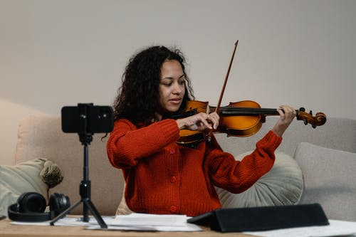 A Person Recording Herself While Playing a Violin