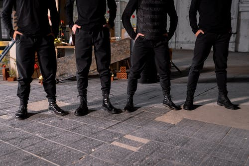 People Standing and Wearing Black Pants and Black Shoes