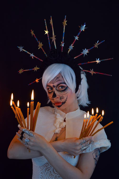 Calm young enchantress with burning candles in black studio